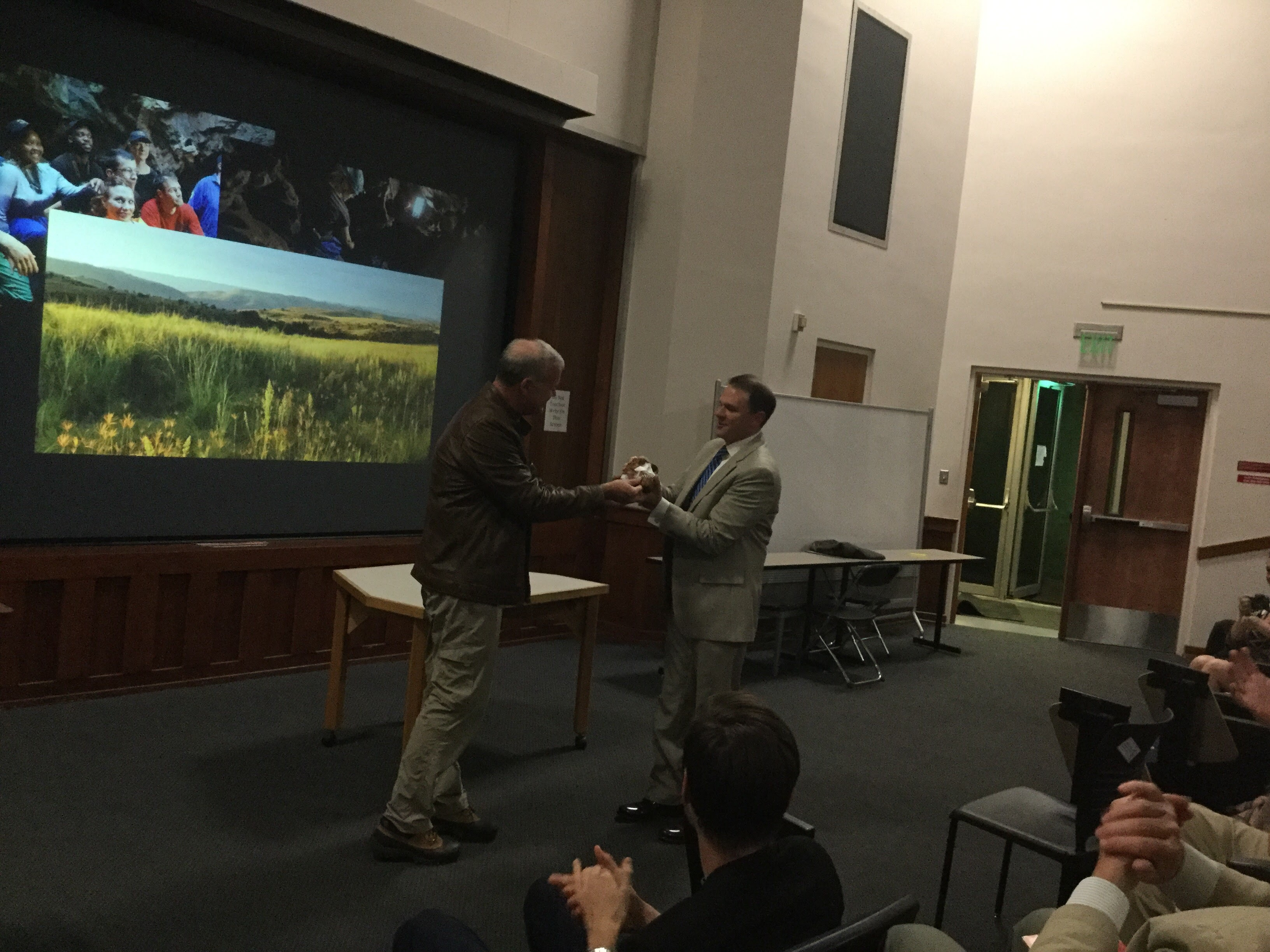 Lee Berger gifts Alabama Natural History Museum Bill Bomar a Homo naledi cast at his ALLELE/ANHM co-sponsored talk.